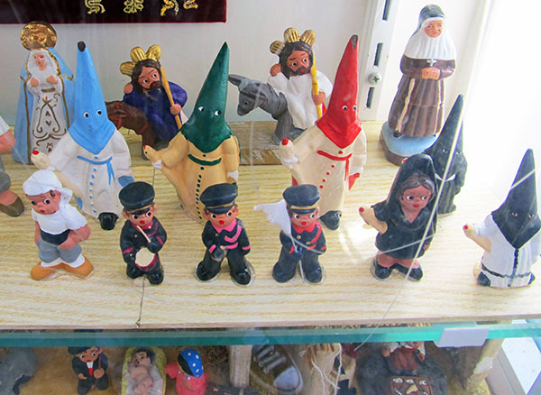 nazarenos among statuettes in a seville old town storefront