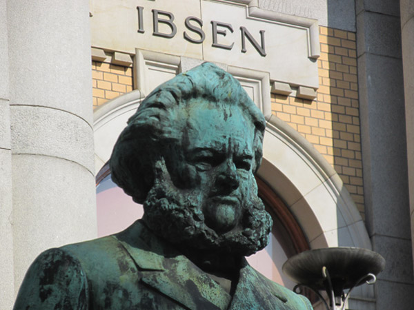 statue of henrik ibsen in front on national theatre in oslo, norway